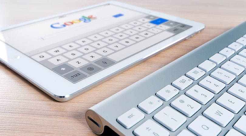 See for Small Businesses - Apple Tablet laying on table with Google Search Engine open with Apple Keyboard in front of it