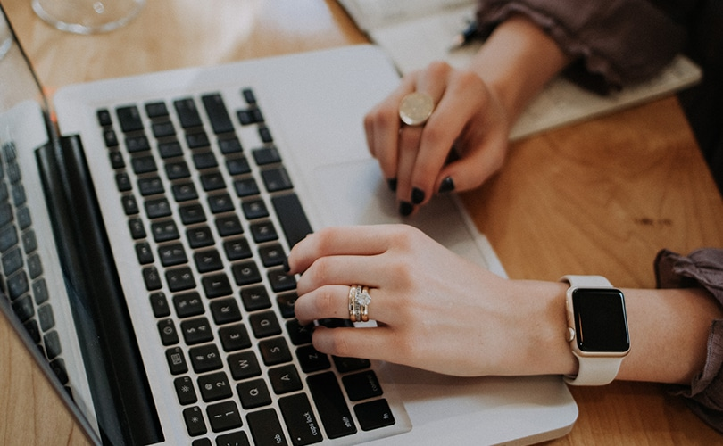 Content Marketing Ideas for Small Business throughout March 2020 - Lady Writing at MacBook Pro with Rings and Apple Watch on