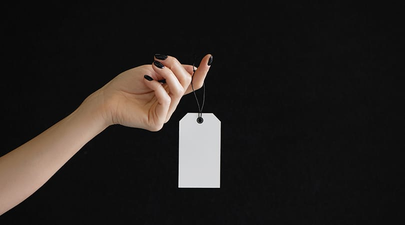 Black Friday For Small Businesses | Black Background with Lady with black nail polish holding a white empty tag | Lorna Scully Digital Marketing Consultant