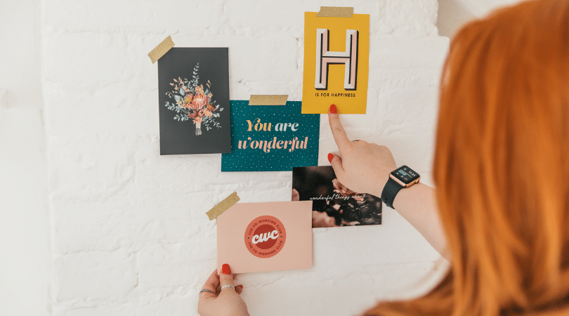 Lorna Scully hand pointing at H is for Happiness postcard on white wall